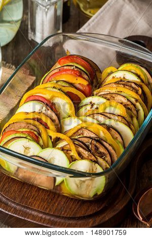 Ratatouille - traditional French Provencal vegetable dish in glass brazier on wooden cutting board