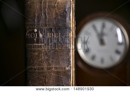 The Holy Bible Next to an Old Clock