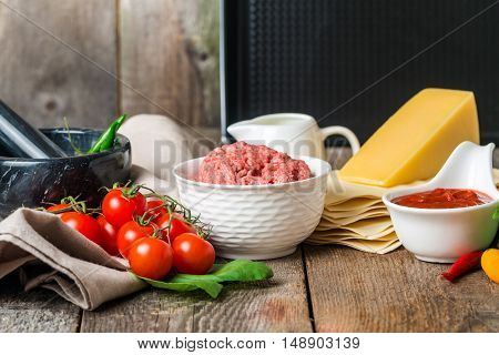 set of ingredients for cooking Italian lasagna on rustic wooden background