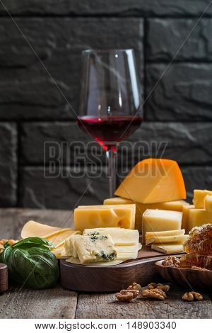 Various types of cheese on cutting board with red wine on wooden background