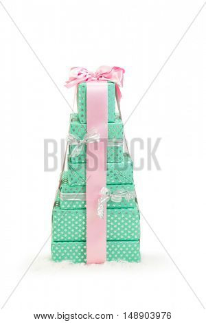 Stack of six christmas presents wrapped in a pink bow