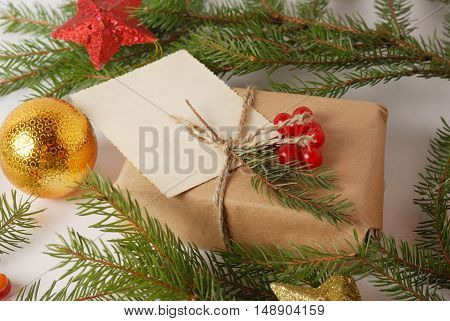 New Year Handicraft wrapping gift box among green pine tree branches and christmas decor balls. Holidays background