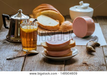 sandwich with boiled sausage and tea glass on rustic wooden background