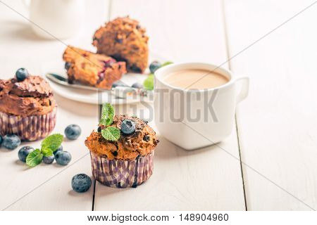 Carrot muffins with blueberrie on white wooden background