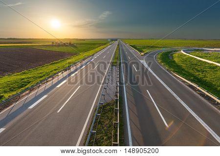 Empty straight highway towards the setting sun at beautiful spring day near Belgeade Serbia.