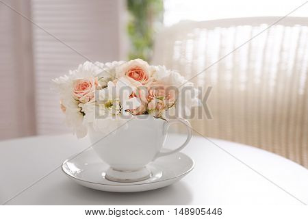Delicate flower bouquet in cup on table