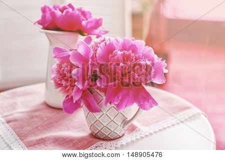 Pink peonies in cup on napkin
