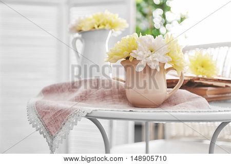 Yellow and white  chrysanthemum in milk jug on napkin