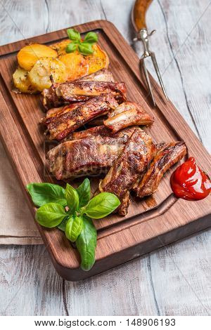 Delicious Grilled Pork Rib and Fried Potato Wedges with Sauce on wooden cutting board, white wooden background