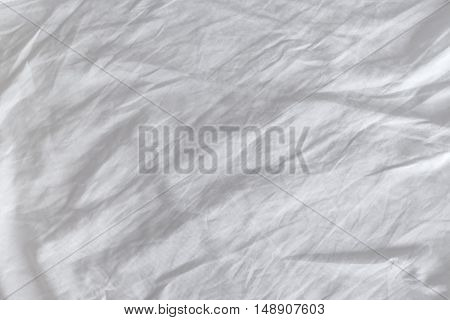 Crumpled white cotton sheets texture top view of wrinkles on an untidy bed.