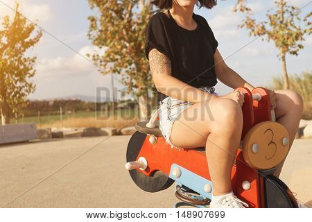 Young slim beautiful woman with tattoos wearing shorts and an unlabeled black t-shirt riding a seesaw motorcycle in a park