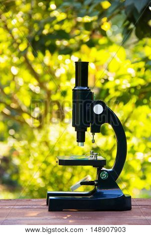 School microscope. Device for the study of biology. The study of nature and the environment. Optical instrument for a young researcher. Microscope on a wooden table against the background of nature.