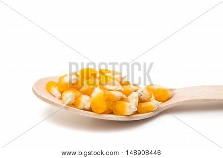 corn in a wooden spoon isolated on white background
