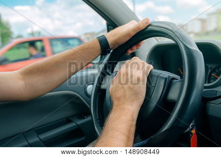 Nervous male driver pushing car horn in traffic rush hour close up with selective focus on hand on the steering wheel