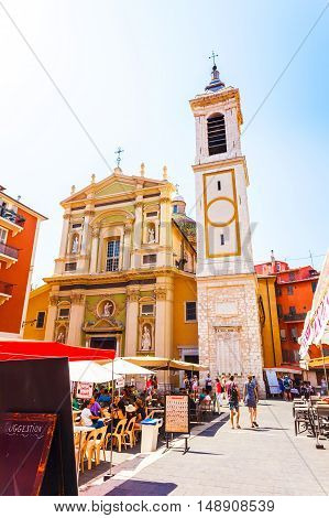 NICE, FRANCE - AUGUST 28, 2016: The cozy patio with a church in the old part of Nice. Square with lots of cafes, tables and dining crowd. A small fountain in the foreground between the tables.