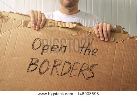 Male refugee holding cardboard with handwritten Open the borders request