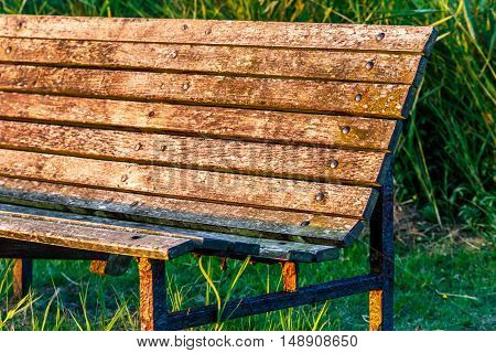 Wooden bench in park with bright yellow sunset light for concept use