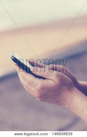 Retro toned adult female hands using mobile phone outdoors everyday usage of electronic device for communication selective focus
