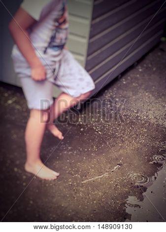 Boy outside splashing jumping in fresh puddles