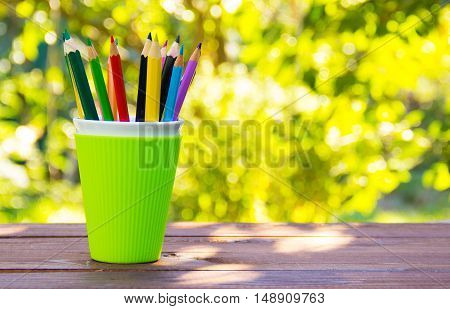 Green glass with colored pencils on the wooden table. Stationery and office supplies. Natural green background.