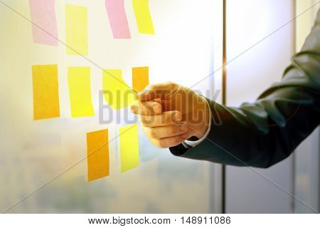 businessman working with stickers on the window in office