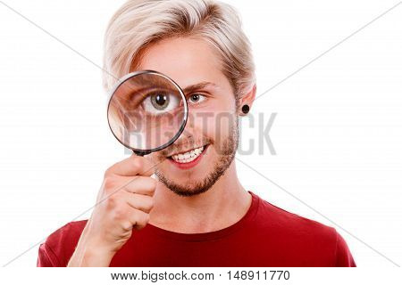 Investigation exploration education concept. Young smiling man holding on eye magnifying glass looking through loupe isolated on white