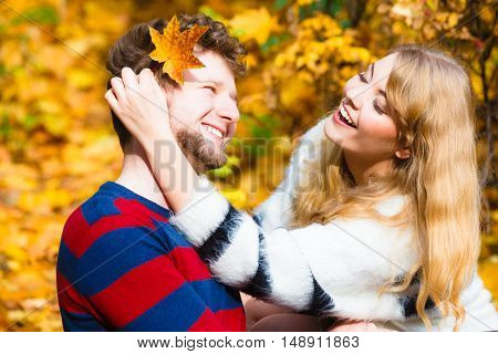 Concepts of autumn love togetherness and relationship. Young romantic couple sitting on bench hugging in autumnal park on sunny day