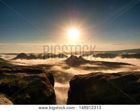 bright orange daybreak. Sandstone cliff above deep misty valley in Saxony Switzerland. Hilly peaks sticking out from creamy fog.
