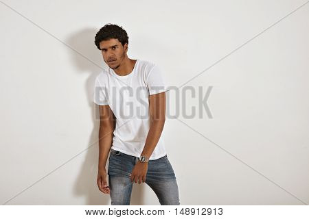 Young serious looking black model in jeans and blank white t-shirt moving away from the camera against a white wall