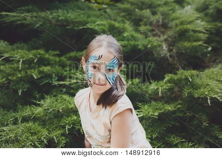 Small girl portrait with funny face art painting. Female child sit in park with blue butterfly drawing on her face. Children event, birthday party and modern creative entertainment.