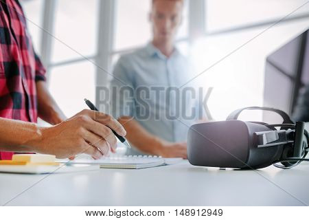 Virtual Reality Glasses On Table With Men Working