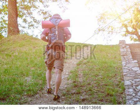 Trekker walking on a mountain path in a sunny day