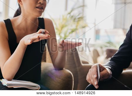 Young Woman Explaining Business Idea To Businessman