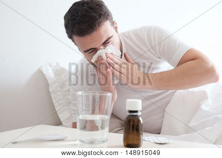 Man feeling cold lying in the bed and blowing his nose