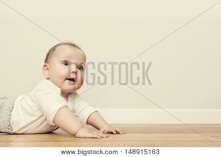 Cute happy baby crawl on wooden floor and smiling. Vintage. Copy-space on the wall.