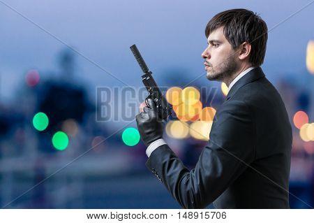 Secret Agent Or Spy Holds Pistol In Hand At Dusk.