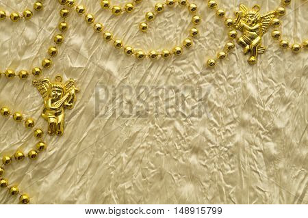 Wedding or celebration background with golden beads and angel figures on the white silk textile