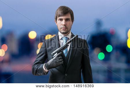 Mafia Man Or Racketeer With Pistol With Silencer In Hand At Dusk