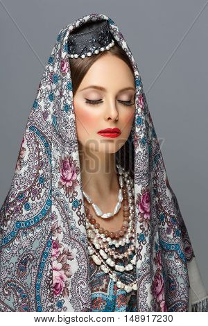 Beautiful young woman with make-up in traditional Russian clothes. Pearl accessories, hat and shawl. Closed eyes. Over grey background. Copy space.