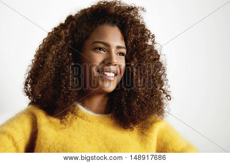 Black Woman Wears Sweater. She Is Smiling And Watching Aside