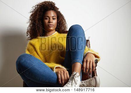 Black Woman Wears Yellow Flyffy Sweater Sitting In Chear