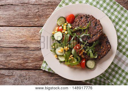 Black Bean Burger With A Salad Of Fresh Vegetables Closeup. Horizontal Top View