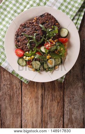 Black Bean Burger With A Salad Of Fresh Vegetables Closeup. Vertical Top View