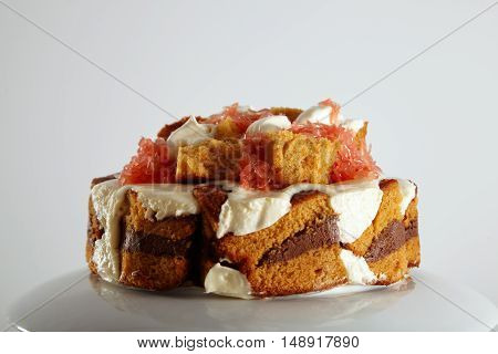 Close up shot of a delicious mouthwatering brown sponge cake with chocolate filling, cream and grapefruit