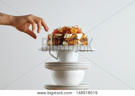 A hand reaching out to grab a piece of beautiful light brown sponge cake with chocolate and cream and grapefruit