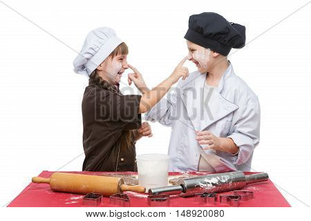 Beautiful boy and girl in chef clothes making christmas cookies with plunger over white background. Isolated. Copy space.