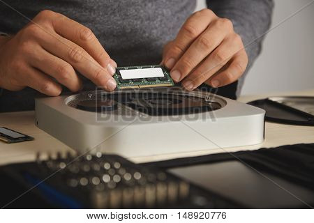 Close up shot of a well dressed fit man installing RAM chips into a computer