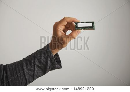 Man in dark gray long sleeve t-shirt holding a memory chip with no label isolated on white, close up