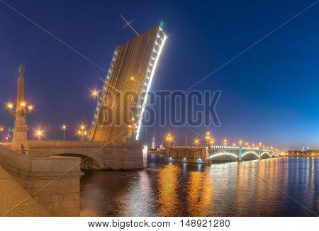 Night view of illumunated open Trinity Bridge and Neva River, St. Petersburg, Russia