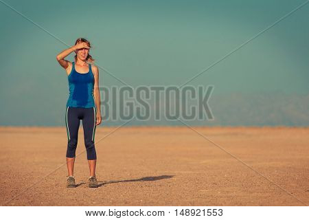 Young woman in wet clothes standing in the desert